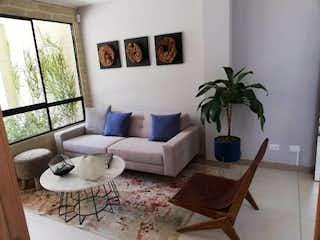 Una sala de estar llena de muebles y una planta en maceta en  TIVOLI