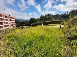 Una vista de un campo de hierba con un edificio en el fondo en Lote en Venta EL RETIRO