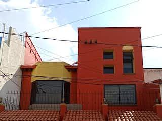 Un edificio de ladrillo rojo con un banco rojo en frente en CASA EN VENTA EN BARRIO 18