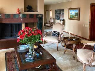 Una sala de estar llena de muebles y flores en Apartamento En Venta En Bogota El Refugio