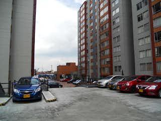 Una calle de la ciudad llena de coches y edificios estacionados en Apartamento En Venta En Bogota El Tintal