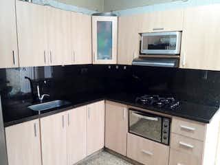 Una cocina con armarios blancos y electrodomésticos negros en Casa en venta en Manrique Central de 119mts