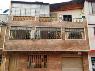 Un gran edificio de ladrillo con un reloj en él en Vendo casa rentable sector Restrepo