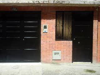 Un edificio de ladrillo con una ventana y una puerta en Casa en Madrid, Cundinamarca - Dos alcobas