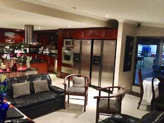 Una sala de estar llena de muebles y una televisión de pantalla plana en Bogota, Venta Casa en San Jose de Bavaria 370 mts