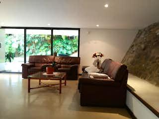Un gato sentado en un sofá en una sala de estar en PIEDRA VERDE