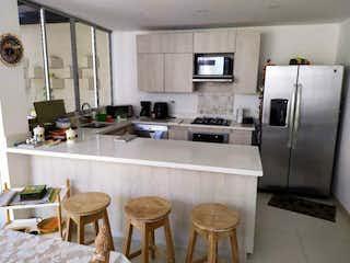 Una cocina con una mesa y una nevera en Casa en venta en Llanogrande, de 130mtrs2