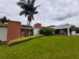 Una casa con un árbol y una casa en Finca en Venta EL RETIRO