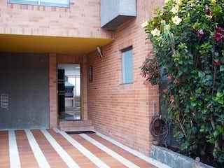 Un edificio de ladrillo con un banco rojo delante de él en Casa En Venta En Bogota Icatá