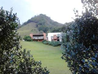 Una casa con un árbol en el medio en Finca En Rionegro Llanogrande, Casa en venta en Centro de 4 alcobas