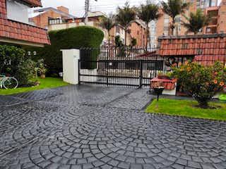 Una calle de la ciudad con un banco y árboles en Vendo Casa Cedritos Bogotá