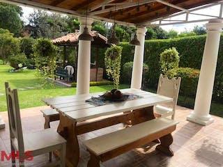 Una mesa de madera y sillas en un parque en Gualanday