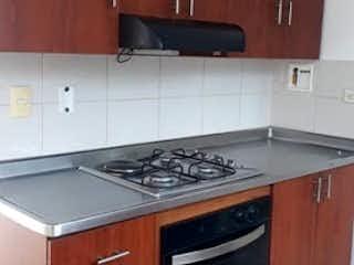 Una cocina con armarios de madera y un horno negro en Apartamento en Venta PROVENZA