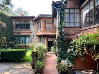 Un gran edificio con una planta en maceta en Exclusiva Casa Colonial en el corazón de San Ángel Inn