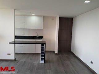 Una cocina con suelo de madera y armarios blancos en Capella