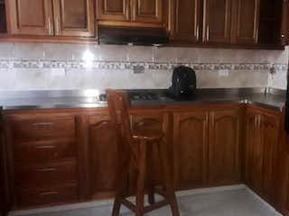 Una cocina con armarios de madera y electrodomésticos de acero inoxidable en Casa en venta en Parque/Centro de 4 alcobas