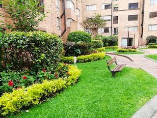 Un banco del parque sentado en medio de un jardín en Apartamento En Venta En Bogota Salitre