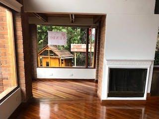 Una sala de estar con suelos de madera y una ventana en Se Vende Casa en San José de Bavaria