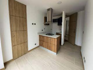 Una cocina con suelo de madera y armarios blancos en Apartamento en venta en Casco Urbano El Retiro de 2 hab.
