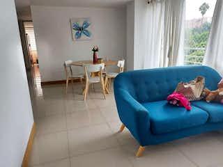 Un sofá azul sentado en una sala de estar junto a una ventana en Apartamento en Venta LA PILARICA