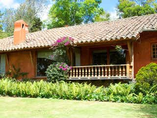 Un edificio de madera con un gran jardín de flores en En Bogota Vendo Casa Por El Antiguo Camino A Suba