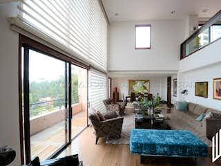 Una sala de estar llena de muebles y una gran ventana en VENTA ESPECTACULAR Y EXCLUSIVA CASA EN BOSQUE MEDINA