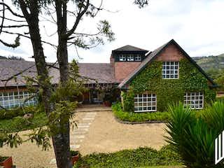 Una casa que tiene una casa en el fondo en CASA CAMPESTRE PARA VENTA. URBANIZACIN TEUSAC (VIA LA CALERA).