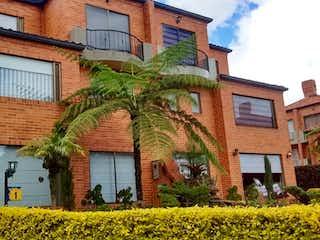 Un edificio con un árbol delante de él en AMPLIA Y HERMOSA CASA EN CHIA- VENTA