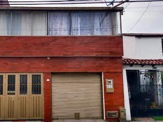 Un edificio de ladrillo rojo con una puerta roja en Casa En Venta En Bogota Villa Luz