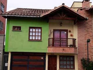 Un edificio de ladrillo con una puerta verde y una ventana en SE VENDE CASA UNIFAMILIAR EN UNI ABIERTA RIONEGRO