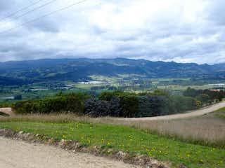 Una vista de un campo con una montaña en el fondo en Lote En Venta En Chia Yerbabuena