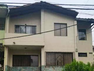 Un edificio blanco con un reloj en el costado en Casa lote en venta barrio Girardot medellin Colombia