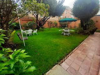 Un banco sentado en la hierba cerca de una casa en Casa En Venta En Bogota Navarra-Usaquén