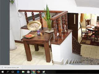 Un reloj sentado en la parte superior de la mesa de madera en Casa En Venta En Bogota Normandia