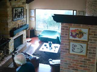 Una sala de estar llena de muebles y un reloj en Casa Campestre En Venta En Chia Vereda Yerbabuena