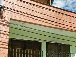Un banco verde sentado delante de un edificio en Casa en Venta LA SEBASTIANA