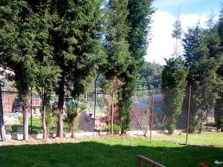 Un banco de madera sentado en medio de un parque en Casa En Venta En Chia Valvanera