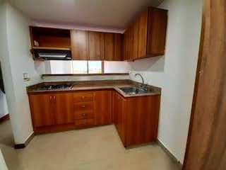 Una cocina con armarios de madera y electrodomésticos blancos en Apartamento en venta en Villa Nueva con Zonas húmedas...