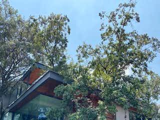 Una casa que tiene un árbol delante de ella en VENTA RESIDENCIA JARDINES EN LA MONTAÑA, ZONA SUR CDMX