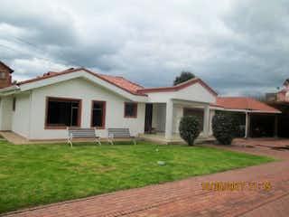 Una casa que tiene una casa en ella en Casa campestre en Chia-La Balsa con hall de alcobas grande.