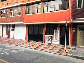 Un edificio de ladrillo rojo con una puerta roja en VENDO CASA RENTABLE LA FLORIDA