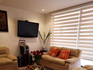 Una sala de estar llena de muebles y una televisión de pantalla plana en Apartamento en venta en Cedritos de 3 habitaciones
