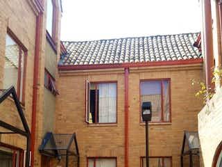 Un edificio de ladrillo con una puerta de madera y un banco en VENDO CASA CEDRITOS EN CONJUNTO RESIDENCIAL
