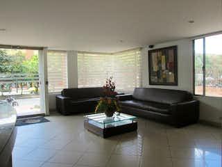 Una sala de estar llena de muebles y una gran ventana en Apartamento en venta en Caobos Salazar de tres habitaciones