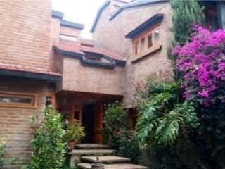 Un edificio de ladrillo con un jardín de flores en él en Casa en Venta en San Nicolás Totolapan
