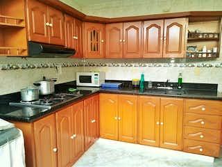Una cocina con armarios de madera y electrodomésticos negros en Venta de casa en Itagui Asturias