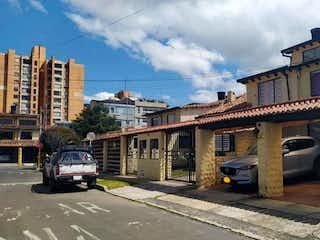 Un coche conduciendo por una calle al lado de edificios altos en Casa En Venta En Bogotá La Colina Campestre
