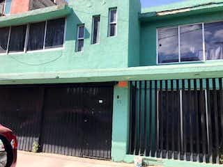 Un edificio verde y blanco con una ventana en EN VENTA AMPLIA CASA, COLONIA APATLACO IZTAPALAPA