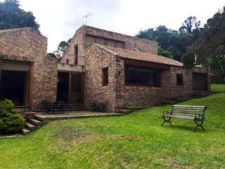 Un banco delante del edificio de ladrillos en Casa en venta en Altos De Chozica de 3 alcoba