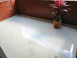Un jarrón de flores sentado en el suelo de azulejos en Se vende amplio apartamento en el centro de Medellin